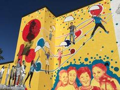Mural going up in North Danville showing kids floating to a better future